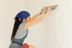 贴墙纸墙壁的妇女 免版税库存图片