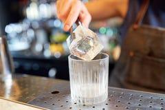 增加冰块的侍酒者入玻璃在酒吧 图库摄影