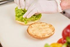 增加在汉堡的厨师莴苣叶子 免版税库存图片