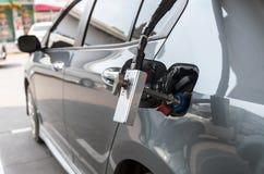 增加在汽车的气体的气管在加油站 免版税库存图片