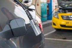 增加在汽车的气体的气管在加油站 库存图片