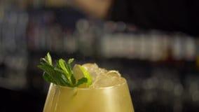 增加在酒精黄色饮料的男服务员新鲜薄荷叶子与冰块 影视素材