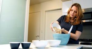 增加成份的妇女到烘烤的碗 影视素材