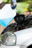 增加挡风玻璃在汽车的洗衣机流体 免版税库存照片
