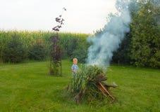 增加木头的一个年轻小伙子到闷燃的后院火 图库摄影