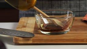 增加橄榄油和香料为与vegies食谱的一个鳄梨调味酱捣碎的鳄梨酱做准备 股票视频