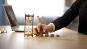 增加硬币的妇女到在办公桌,银行收入兴趣,投资上的堆 免版税图库摄影