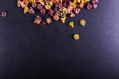 增加自然植物染料的多彩多姿的面团 驱散在一张黑具体桌上 顶视图,拷贝空间 库存图片