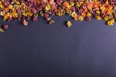 增加自然植物染料的多彩多姿的面团 驱散在黑背景,拷贝空间 顶视图,样式 免版税库存图片