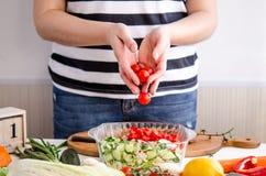 增加菜的妇女手到盘 免版税图库摄影