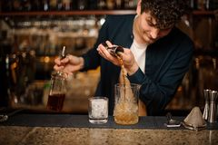 增加酒精饮料的深色的侍酒者入与冰的一块玻璃 免版税库存图片