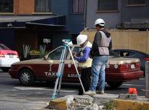 墨西哥城,墨西哥- 2015年11月27日:工作在一条路的墨西哥测量员在有出租汽车的墨西哥城在背景中 免版税库存图片