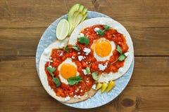 墨西哥早餐huevos rancheros :与辣调味汁特写镜头的煎蛋在平底锅 免版税库存图片