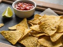 墨西哥烤干酪辣味玉米片切削与辣调味汁调味汁和石灰切片 库存图片