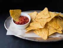 墨西哥烤干酪辣味玉米片切削用在金属片的辣调味汁调味汁在黑暗的背景 免版税库存图片