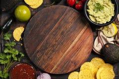 墨西哥烤干酪辣味玉米片切削用自创新鲜的鳄梨调味酱捣碎的鳄梨酱调味汁和婆罗双树 免版税库存图片