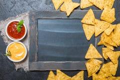墨西哥烤干酪辣味玉米片用调味汁和粉笔板 库存照片