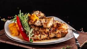 墨西哥烹调的概念 烤猪肉牛排用辣调味汁、红辣椒辣调味汁、桃子和虾 免版税库存图片