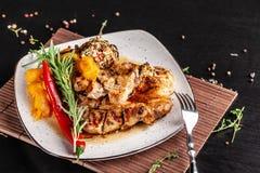 墨西哥烹调的概念 烤猪肉牛排用辣调味汁、红辣椒辣调味汁、桃子和虾 美丽的服务 免版税图库摄影