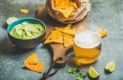 墨西哥玉米片、新鲜的石灰、鳄梨调味酱捣碎的鳄梨酱调味汁和麦子啤酒 免版税图库摄影