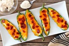 墨西哥胡椒poppers用乳酪和意大利辣味香肠在一块白色板材 免版税库存照片