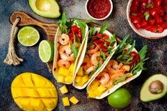 墨西哥虾炸玉米饼用鲕梨,蕃茄,在土气石桌上的芒果辣调味汁 Cinco de马约角党的食谱 免版税图库摄影