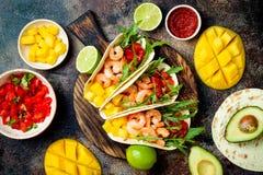 墨西哥虾炸玉米饼用鲕梨,蕃茄,在土气石桌上的芒果辣调味汁 Cinco de马约角党的食谱 免版税库存照片
