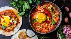 墨西哥食物huevos rancheros 在西红柿酱辣调味汁偷猎的鸡蛋 免版税库存照片