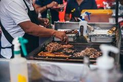 墨西哥- 9月19 :有一个圆环的人在他的手指烹调肉的在墨西哥城的炸玉米饼停留演出地 图库摄影