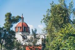 墨西哥- 9月19 :树围拢的古色古香的红色教会圆顶 免版税库存图片