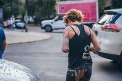 墨西哥- 9月19 :走在有一块残破的挡风玻璃的一辆汽车旁边的被刺字的妇女由于下落的残骸 库存照片