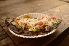 墨西哥tlacoyos,盘做用蓝色玉米和充满油煎的豆或蚕豆,相似与墨西哥gordita,与guacamol 免版税库存照片