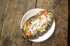 墨西哥tlacoyos,盘做用蓝色玉米和充满油煎的豆或蚕豆,相似与墨西哥gordita,与guacamol 免版税库存图片