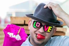 墨镜的一个年轻,浪漫,微笑的人用在他的嘴的题字爱和莓果草莓给花束  库存图片