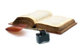 墨水池、笔和在白色背景隔绝的一本老开放书c 库存图片