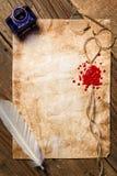 墨水瓶架、羽毛和红色封印在葡萄酒纸 免版税库存图片
