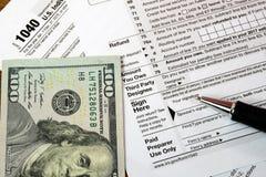 墨水笔和金钱在报税表 免版税库存照片