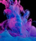 墨水蓝色和桃红色云彩在黑色隔绝的液体的 免版税图库摄影