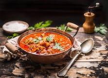墩牛肉或炖煮的食物在铜平底锅有匙子的在土气厨房用桌上在黑暗的木背景 免版税库存照片