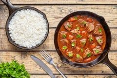墩牛肉自创匈牙利牛肉肉炖煮的食物汤食物烹调用在生铁平底锅膳食的辣小汤调味汁服务用米 免版税库存照片