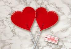 壁纸情人节与红心在典雅的大理石桌上一起隔绝的形状棒棒糖夫妇的贺卡  图库摄影