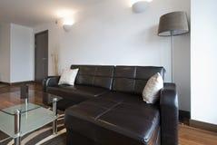 壁角大皮革居住的现代空间沙发 免版税库存照片
