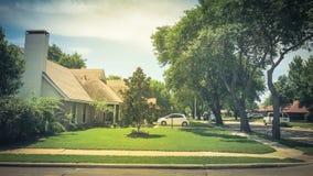 壁角房子在相当有高大的树木机盖和路边路的邻里 免版税库存图片