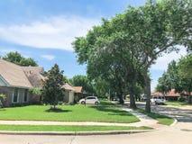 壁角房子在相当有高大的树木机盖和路边路的邻里 库存照片