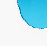 壁角白色被撕毁的纸有蓝色背景 库存图片