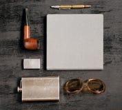 绅士般的集合:威士忌酒、打火机、太阳镜、笔记本、笔和烟斗的烧瓶 库存照片