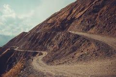 壮观和危险山路, Tusheti,乔治亚 冒险背景双筒望远镜小船概念梯子水 登上风景 未铺砌的弯曲道路 土serpenti 免版税库存照片