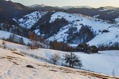 壮观的冬天风景 冬天日落、老农村山木瑞士山中的牧人小屋和多雪的小山在布拉索夫,特兰西瓦尼亚附近 免版税库存照片