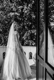 壮观的长的礼服的体贴的新娘在entranc站立 图库摄影