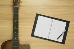 声学吉他和笔记本在木背景 库存图片